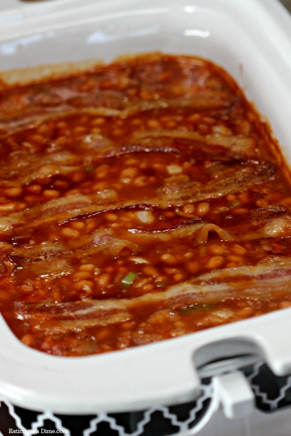 This crock pot baked beans recipe with bacon is amazing! It is the best baked beans recipe in the slow cooker you can make and it's easy too! I love making this recipe for a crowd. If you love slow cooker easy recipes, you are going to love this beans with bacon crockpot recipe! #eatingonadime #crockpotrecipes #sidedishes