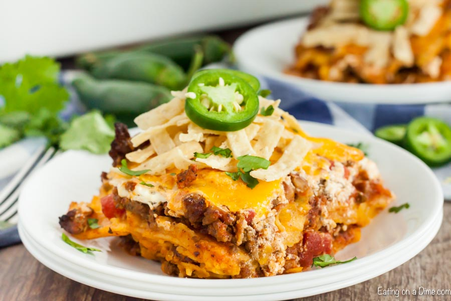 A piece of this Mexican casserole on a plate topped with tortilla strips and sliced jalapeños