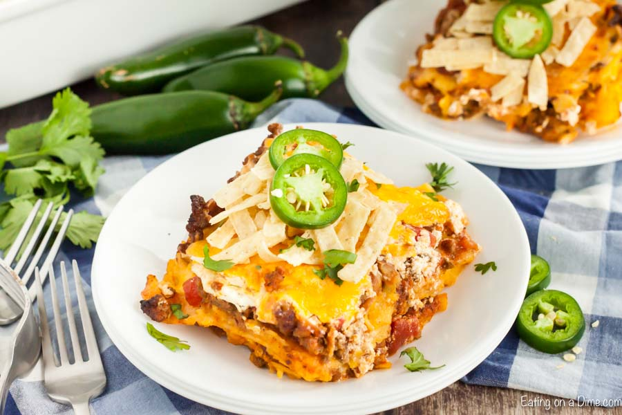A piece of this Mexican casserole on a plate topped with tortilla strips and sliced jalapeños with another piece on a plate behind it