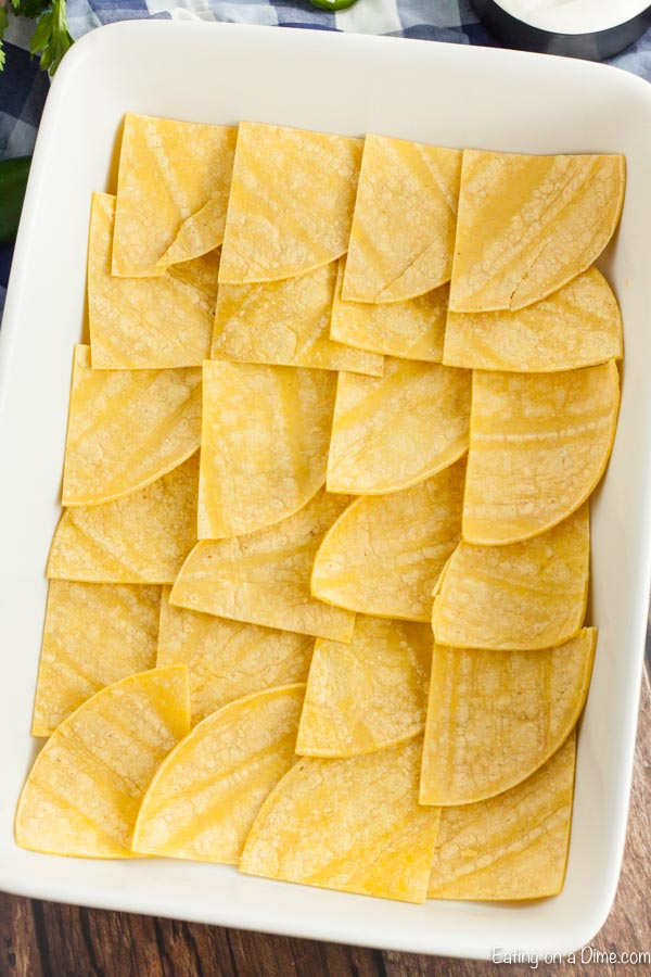 Corn tortillas cut up and laid at the bottom of a 9X13 baking pan.