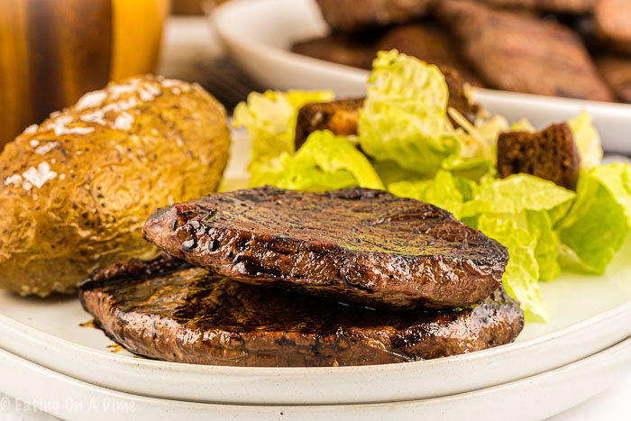 Photo of steak, baked potato and salad on a white plate.