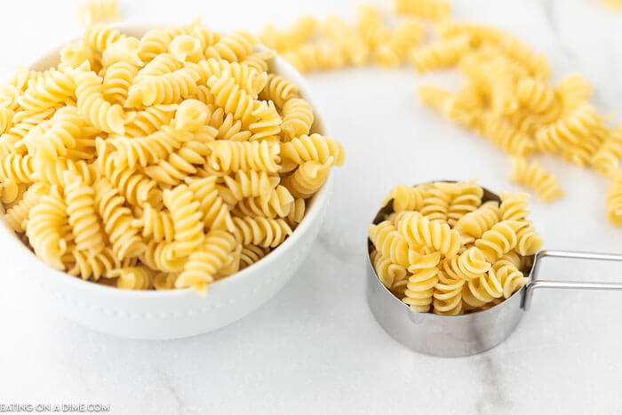 Cooked rotini pasta in a bowl and a measuring cup on a counter.