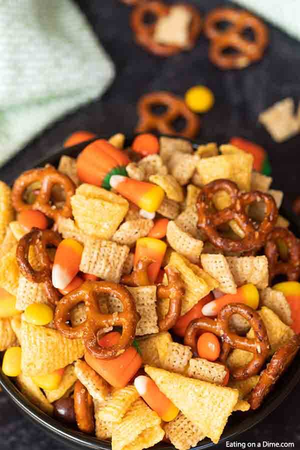 These DIY Halloween Chex Mix is one of my favorite Fall Snacks recipes that is great for kids and for adults! This halloween harvest Chex mix is easy to make and is the perfect combination of sweet and salty with pretzels and candy corn. This is one of the best fall snack ideas! You will love these homemade savory fall Chex mix recipe. #eatingonadime #halloweenrecipes #fallrecipes #snackrecipes
