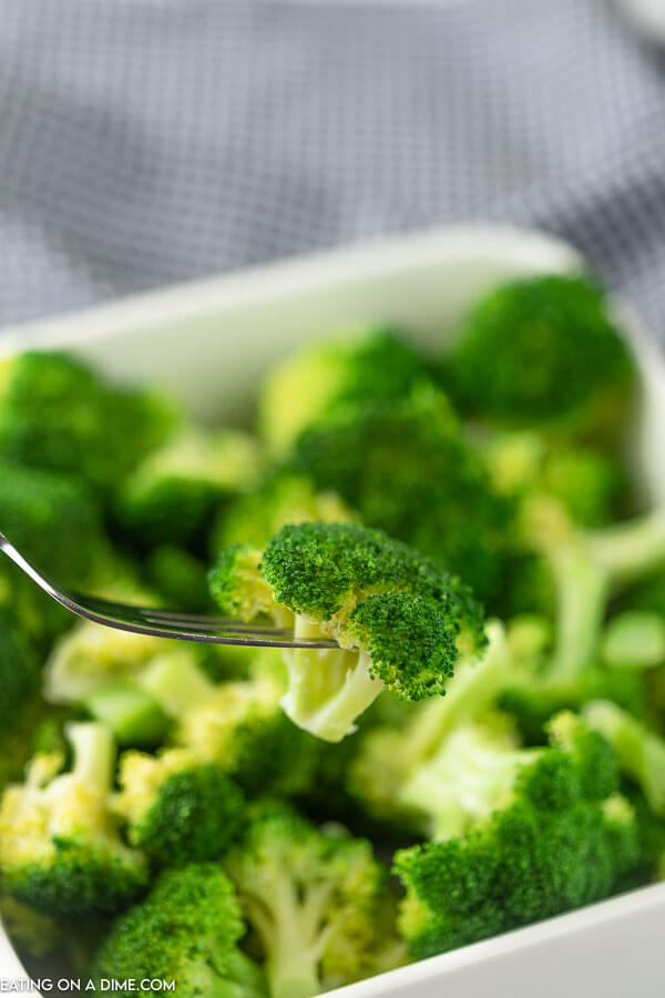 A piece of broccoli being removed from a large bowl of freshly steamed broccoli