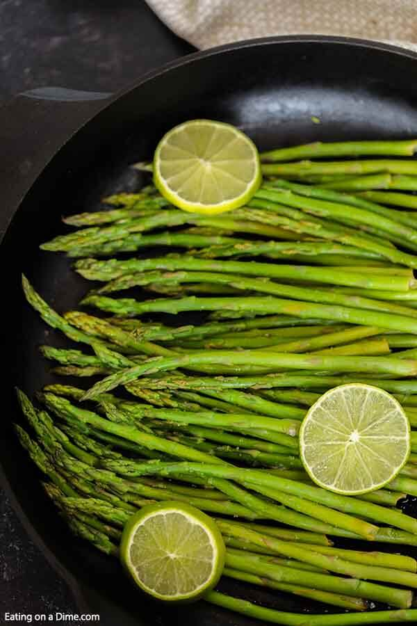 This Garlic Lime Steamed Asparagus is the perfect easy side dish to any meal. Learn how long do you steam asparagus on the stove top for the best Garlic Lime Steamed Asparagus in only 10 minutes. Learn how to make this easy vegetable recipe on stove. This is one of my favorite steamed asparagus recipe. Learn how long to steam asparagus and how to cook asparagus perfectly every time! #eatingonadime #sidedishrecipes #steamedasparagus #easyvegetablerecipes