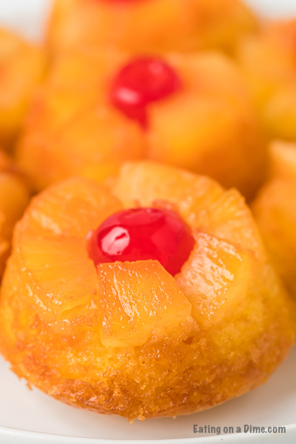 Close up of an Upside Down Pineapple Cupcake on a white plate with another cupcake behind it.
