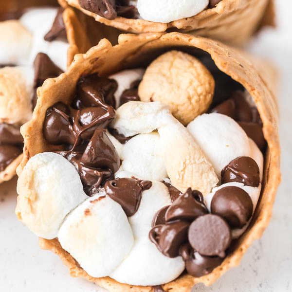 Check out how to make s'mores campfire cones that are fun and less messy than traditional s'mores. Camp fire cones are a blast and fun to make. Campfire sugar cone s'mores are a fun and easy dessert for any camping treat. Campfire s'mores cones will be your favorite summer treat! #eatingonadime #smoresrecipes #campfirecones #easydesserts