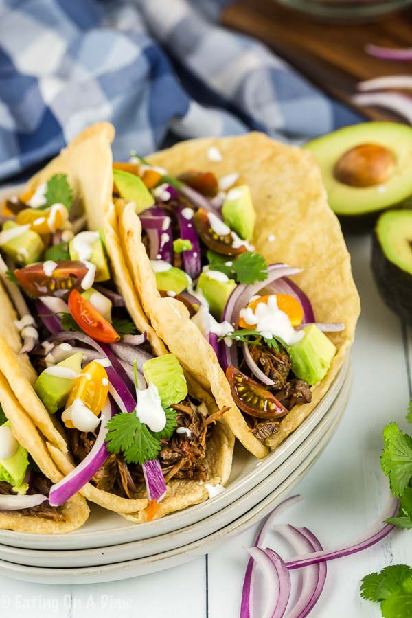 Enjoy Crock pot shredded beef tacos loaded with tender beef. The slow cooker does all of the work and all you need to do is add your favorite toppings!