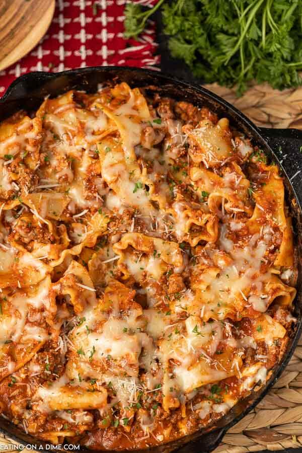 Skillet lasagna topped with shredded parmesan cheese and chopped fresh parsley