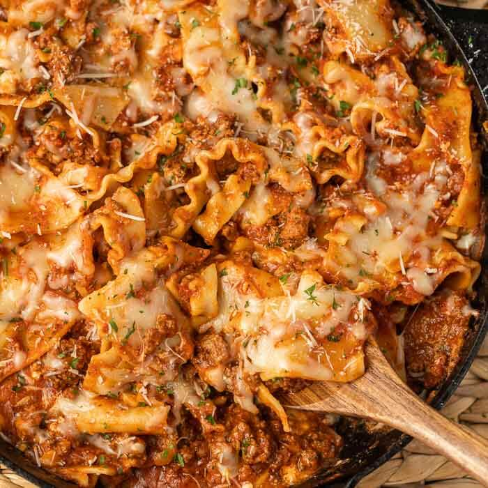 Lasagna in a cast iron skillet on a woven mat with a large wooden spoon in it