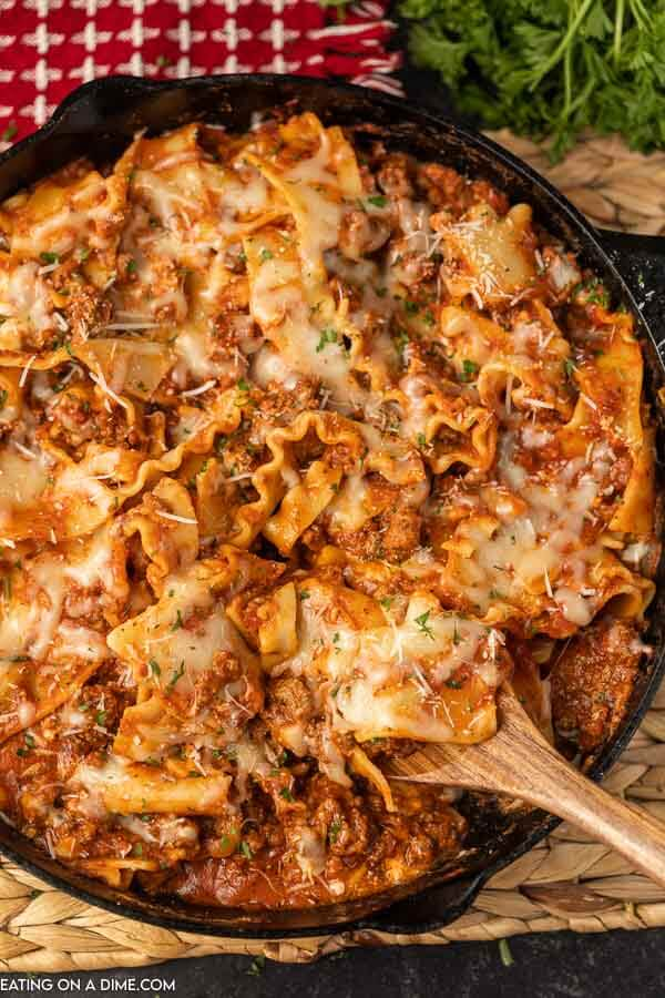 Lasagna in a cast iron skillet with a wooden spoon scooping out a portion of it for serving