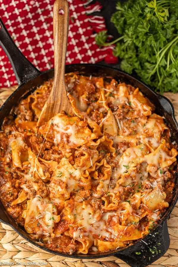Lasagna in a cast iron skillet with a wooden spoon in it with a red linen and fresh parsley in the background.