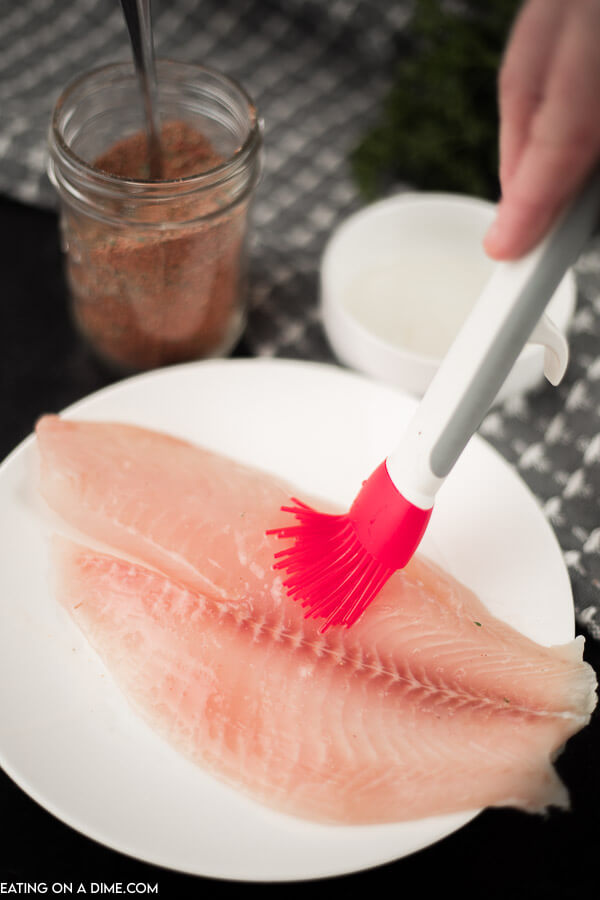 A piece of tilapia on a white plate and a basting brush rubbing vegetable oil on the tilapia