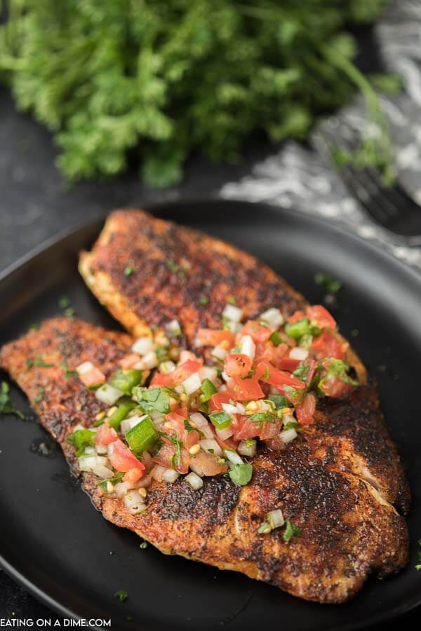 Blackened Tilapia on a black plate topped with pico de gallo