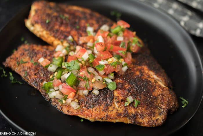 A blackened tilapia fillet on a black plate topped with pico