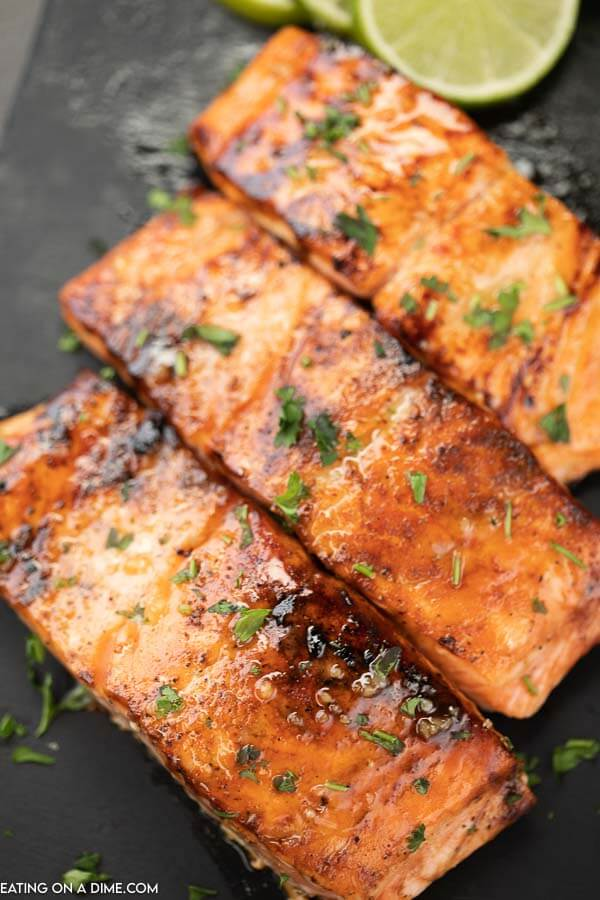 3 pieces of cooked salmon on a black platter topped with parsley