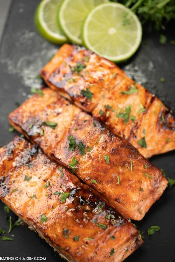 3 pieces of salmon on a black platter with limes in the background and the glaze over the top