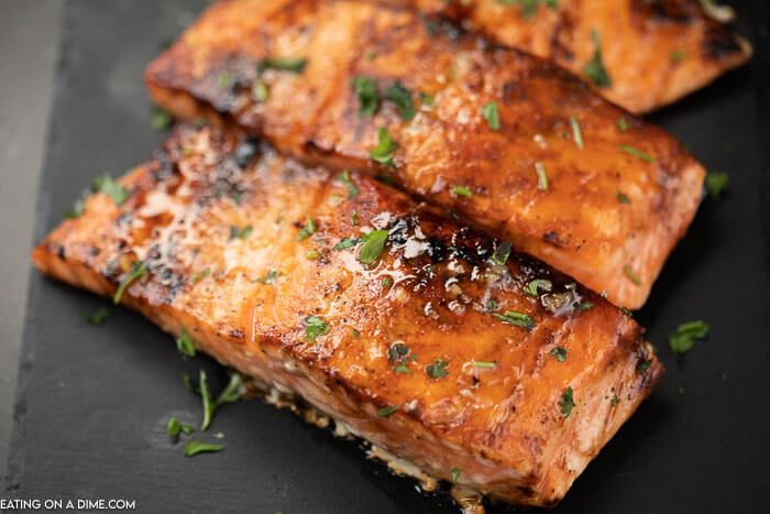 3 pieces of cooked salmon on a black platter topped with parsley with the honey glaze on top