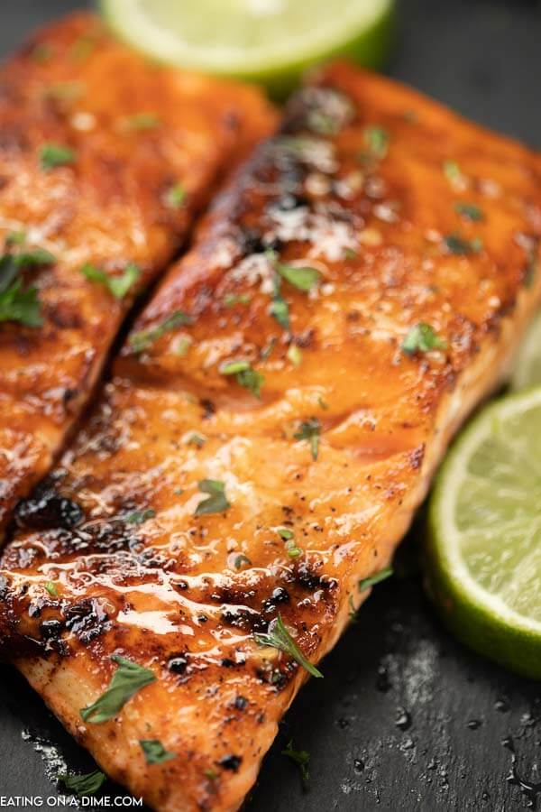 A piece of salmon with the honey glaze on it topped with fresh parsley and limes on the side of it.