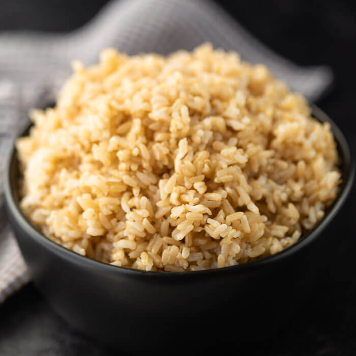 Overview of Cooked Brown rice in a black bowl.