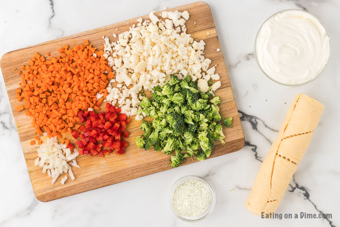 ingredients for crescent roll veggie pizza: carrots, onion, bell peppers, cauliflower, broccoli, ranch, crescent rolls