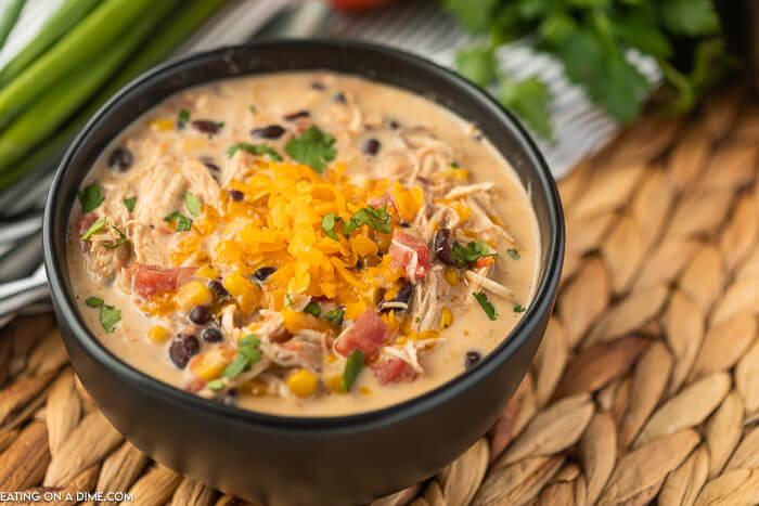 photo of crockpot creamy taco soup in black bowl.