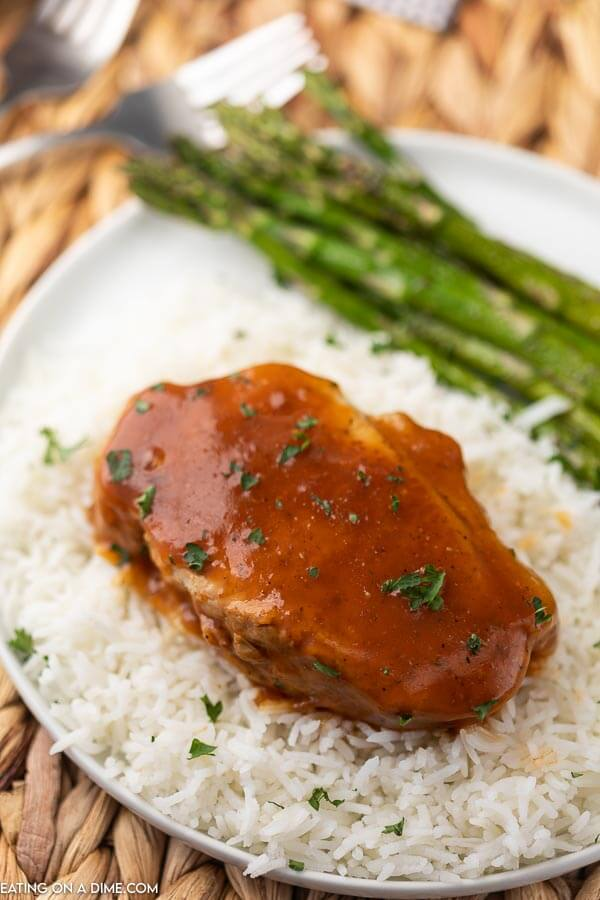 white plate with asparagus, rice and pork chop