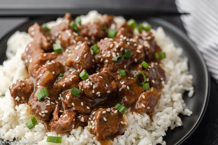Close up of beef teriyaki over rice on a plate.