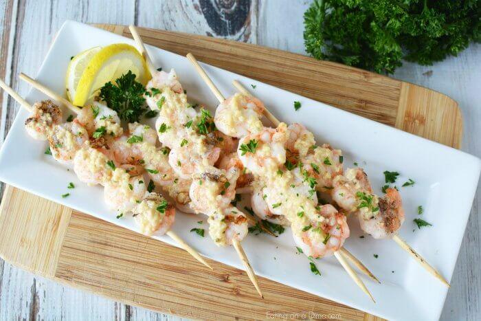 Grilled parmesan shrimp on skewers served on a white platter.