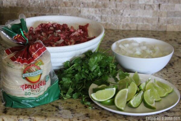 Ingredients needed to make street tacos: steak, tortillas, cilantro, white onions and limes.