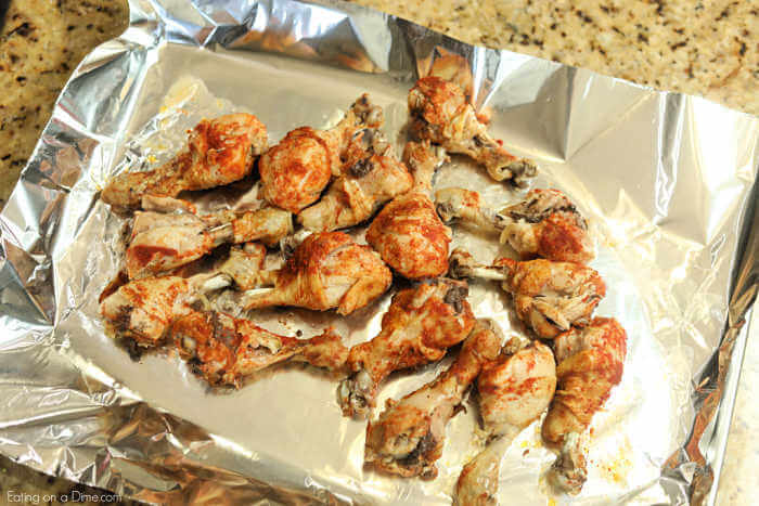 Close up image of BBQ chicken drumsticks on a cookie sheet lined with foil.