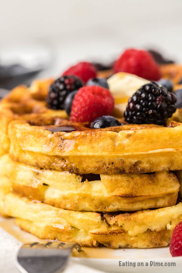 Keto waffle on plate topped with fruit and butter.