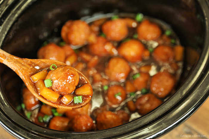 meatballs in a crockpot with a wooden spoon