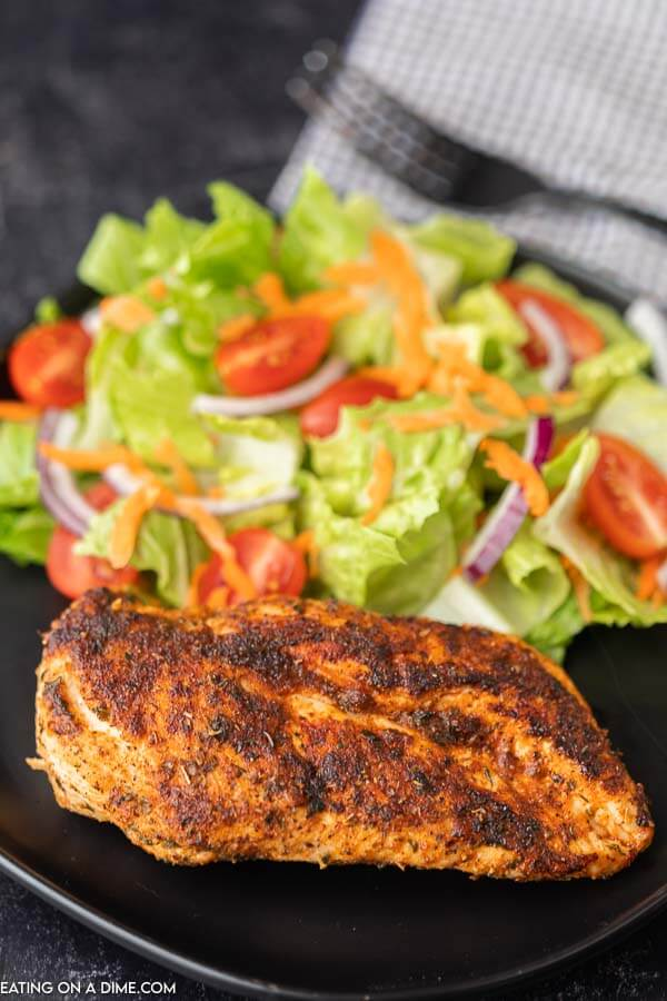 1 blackened chicken breast on a black plate next to a side salad.