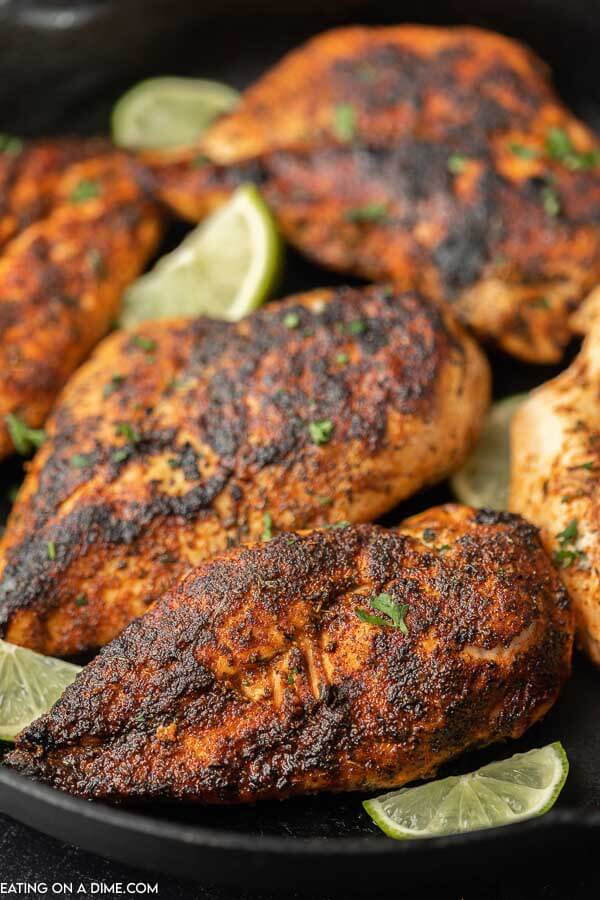 Multiple blackened chicken breasts on a black plate with lime slices on the plate as well.