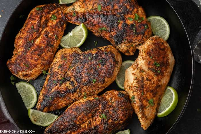 5 pieces of blackened chicken breasts in a cast iron skillet with sliced limes in the pan.
