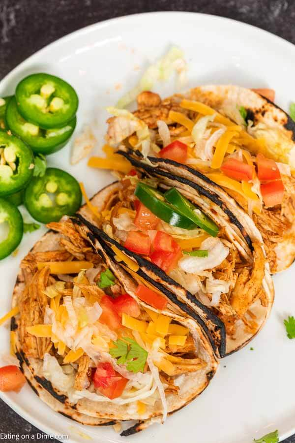 You're going to love this healthy instant pot chicken tacos. This is one of my favorite pressure cooker recipes. This 3 ingredient shredded electric pressure cooker chicken tacos with salsa and taco seasoning is easy to make! You can even make chicken tacos from frozen with this easy recipe that is truly the best! This instant pot recipes easy chicken is perfect for tacos and taco bowls! The entire family will love it! #eatingonadime #instantpotrecipes #pressurecookerrecipes #chickentacos #shreddedchickentacos