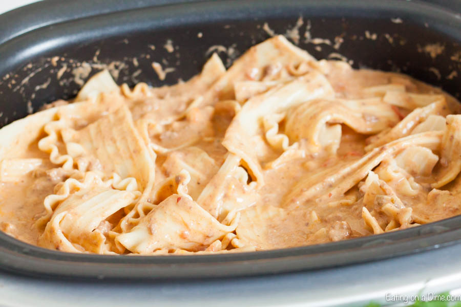 Crock Pot Mexican Lasagna Recipe has layers of delicious cheese, refried beans, beef and more for the best dinner. Let the crockpot do all the work!
