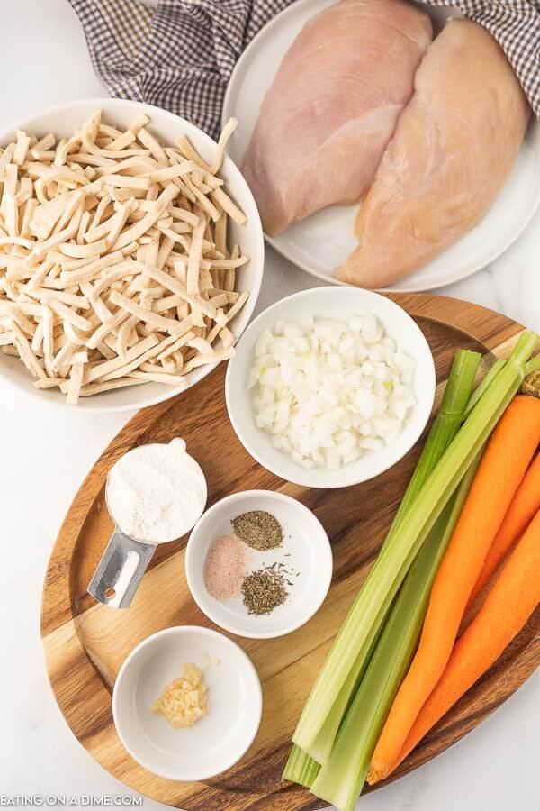 Close up image of ingredients for chicken noodle soup which consist of egg noodles, chicken breast, chopped onions, flour, garlic, seasoning, carrots, and celery.