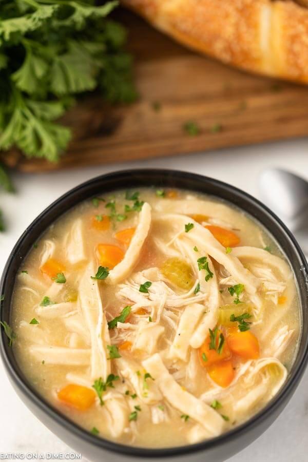 Close up image of a black bowl of chicken noodle soup.