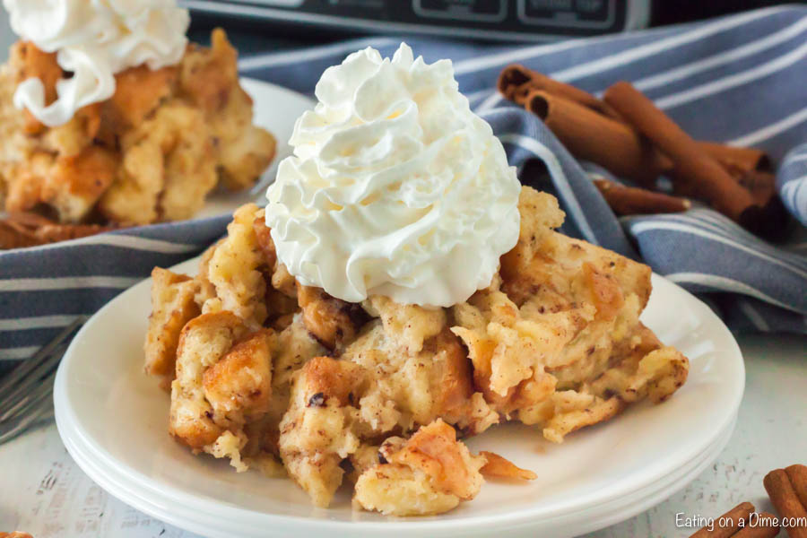 Bread pudding on a plate topped with ready whip with cinnamon sticks behind it.