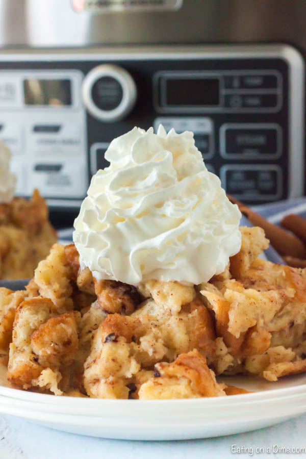Close up of bread pudding on a plate topped with ready whip in front of a crock pot.