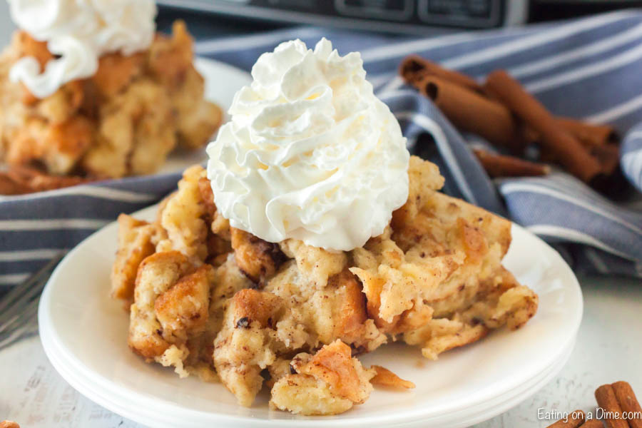 Close up of Bread pudding on a plate topped with ready whip.