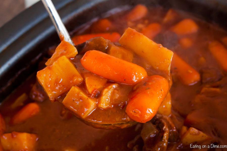 Ladle of Irish beef stew in crockpot.