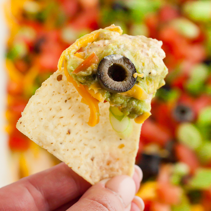 7 layer dip recipe is a crowd pleaser and easy to make. Layers of refried beans, salsa, guacamole and more make this a great dip for parties and tailgating.