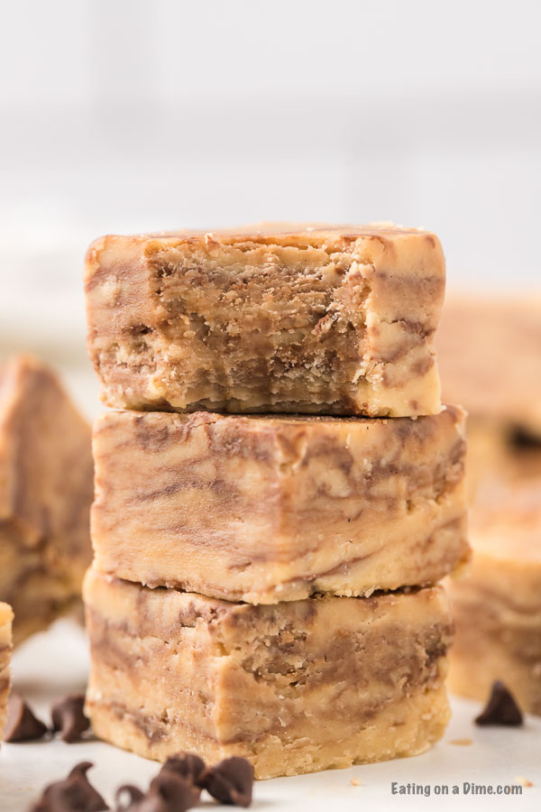 Pieces of peanut butter chocolate chip fudge stacked on top of each other with a bite taken out of the top piece.