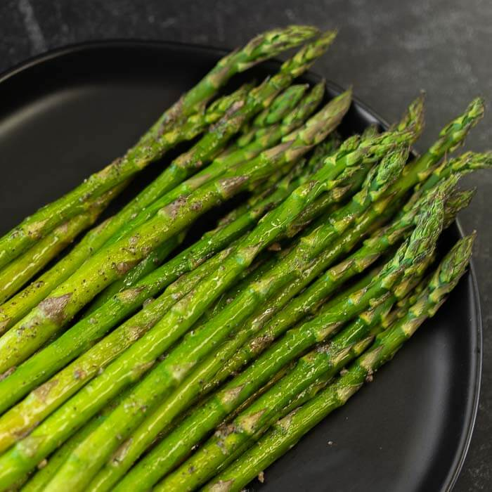 Lots of roasted asparagus on a black plate