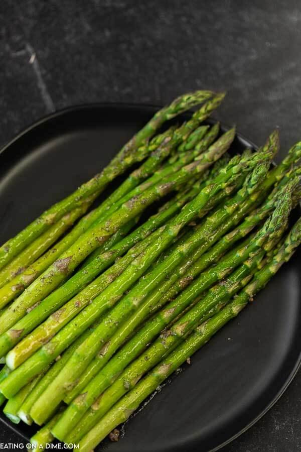 Roasted asparagus on a black plate