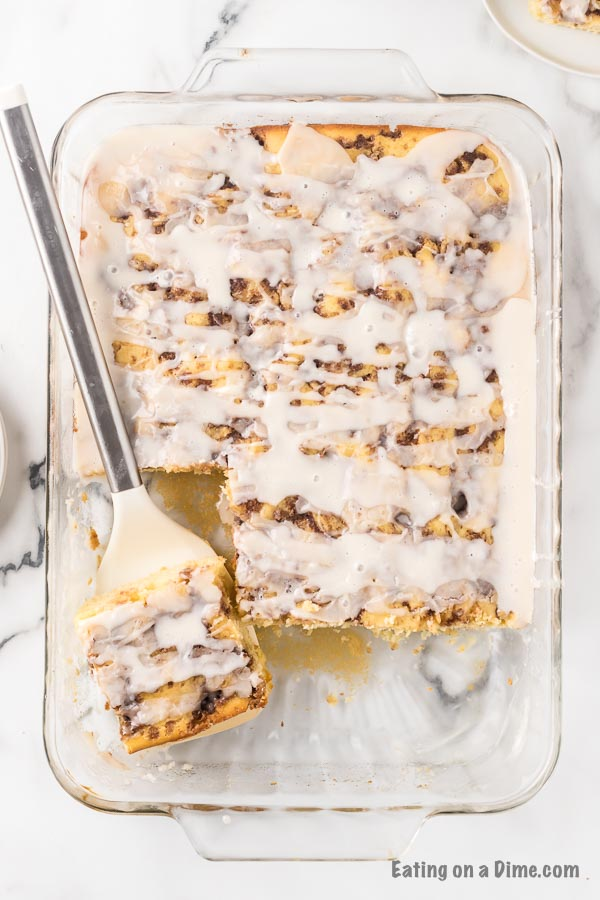 Overview of the cinnamon roll cake in a glass pan with the glaze drizzled on top of it with a piece being served out of it.