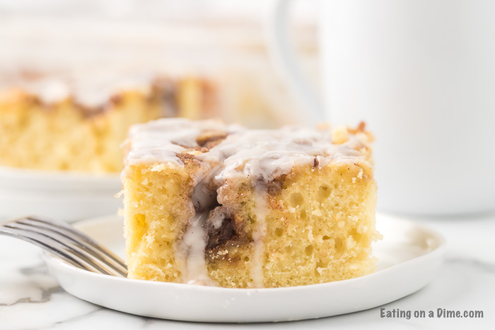 A piece of the cinnamon roll cake on a white plate with a fork with the rest of the cake in the back ground.